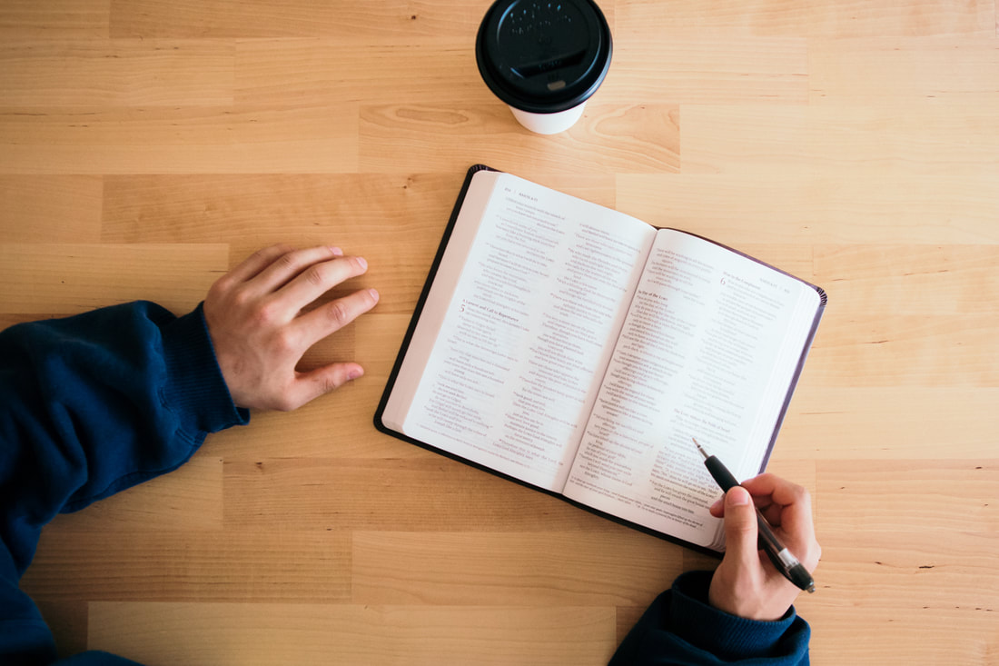 Student studying his bible on a table, with a coffee